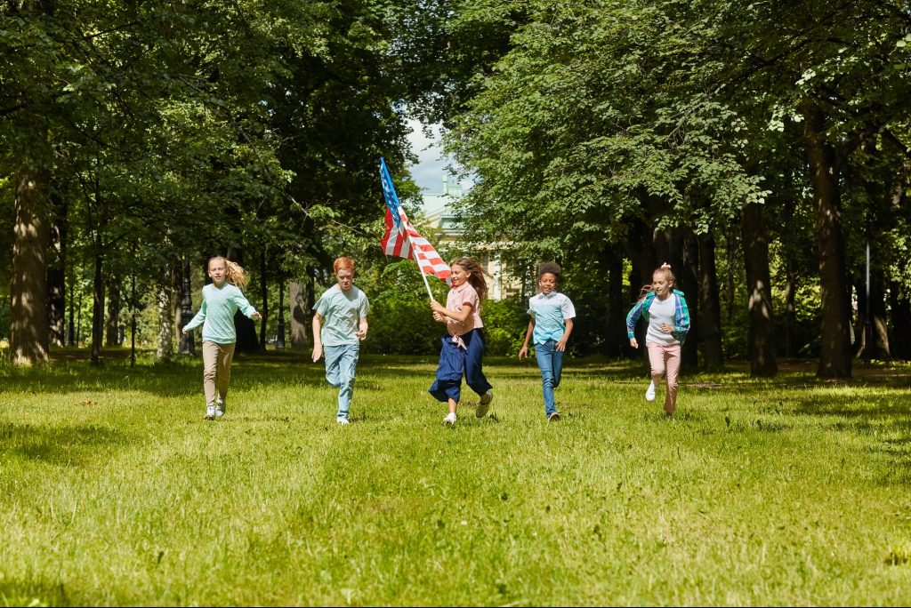 Kids Running with American Flag Outdoors